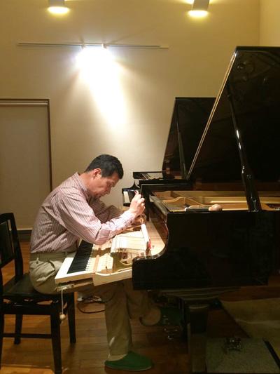 ピアノ整音中の調律師